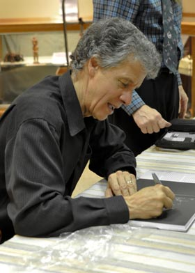 Phil Borges signs a photograph after his lecture Oct. 1. His work focuses on indigenous cultures and human rights issues.