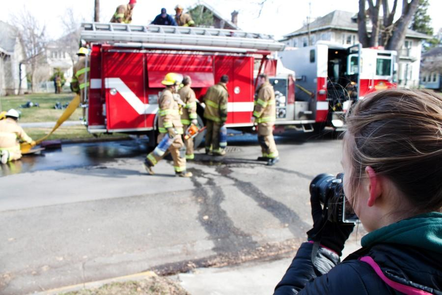 Firefighters respond to a house fire which occured in a Whitman rental house last weekend. The house was being rented by a Whitman professor at the time of the fire. Kendra Klag, a Whitman Pioneer photojournalist, is featured in the foreground. Credit: Ethan Parrish