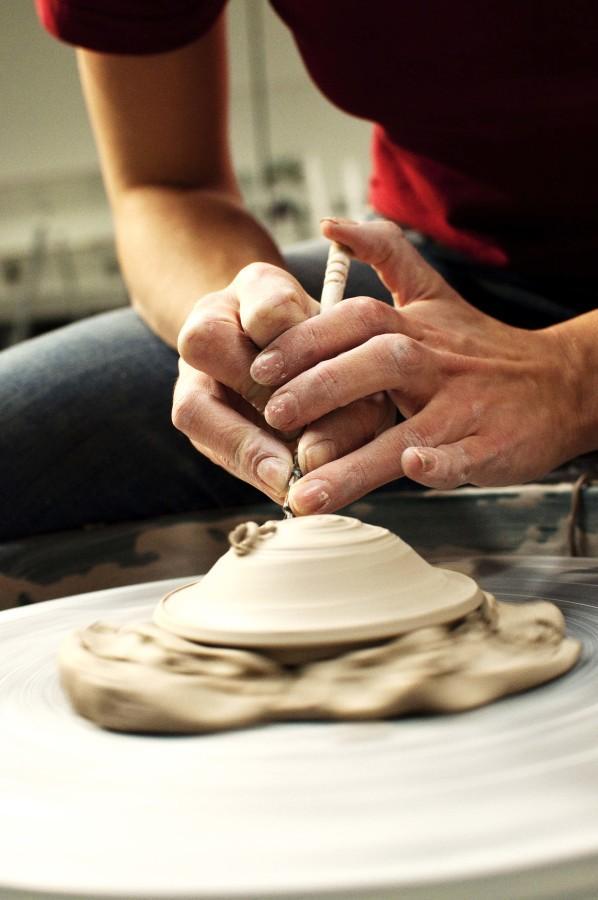 Shannon Flood 11 works on her tea pot tops for advanced independent study ceramics. Credit: Kendra Klag