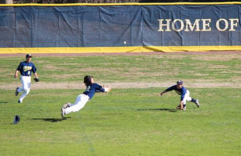 Vela (center) dives for a ball in center field. Photo by John Lee.