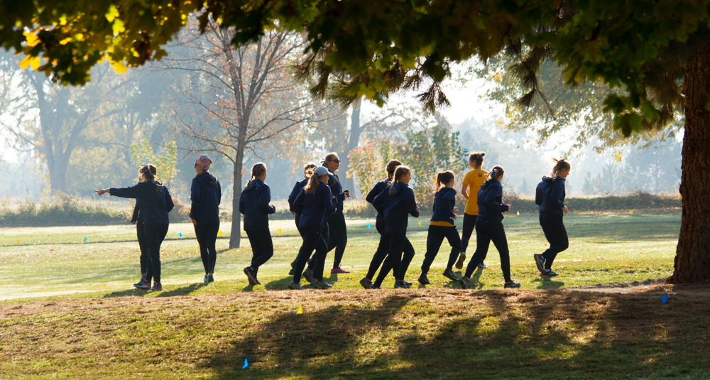 The+women%27s+team+runs+warmup+laps+around+the+golf+course+in+the+early+morning+fog.+Photo+by+Natalie+Mutter
