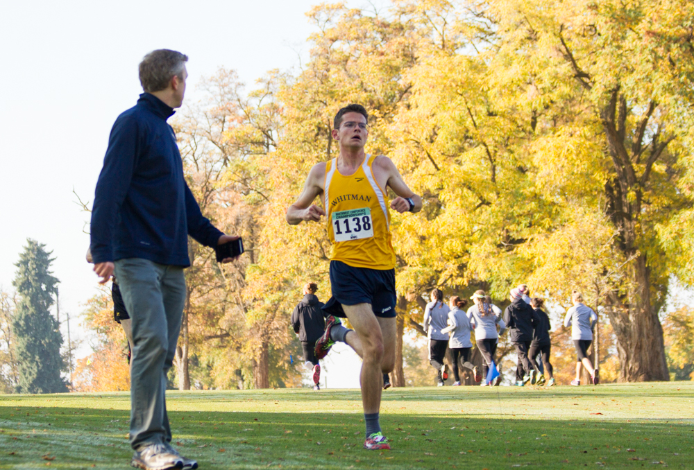Assistant+coach+Neal+Christopherson+offering+encouragement+and+pacing+advice+to+senior+Will+Mullins+%2814th%2C+time+of+26%3A41.1%29+at+the+beginning+of+the+last+lap.+Photo+by+Natalie+Mutter
