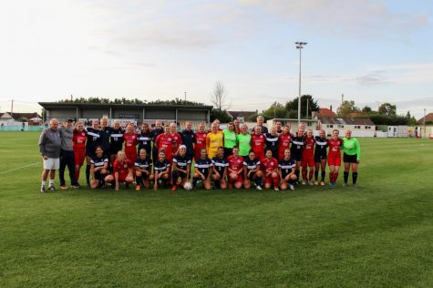 The women's team poses with Frome Town FC, an English football club, after their match. Photo contributed by Whitman Athletics.