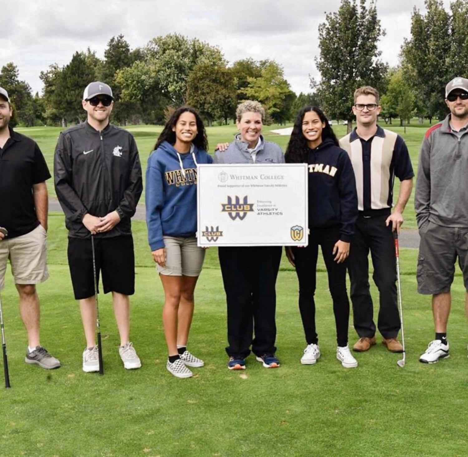 First-year basketball players Caira Young and Shaira Young pose with Kim Chandler and participants of the W Club golf tournament. Photo contributed by Shira Young